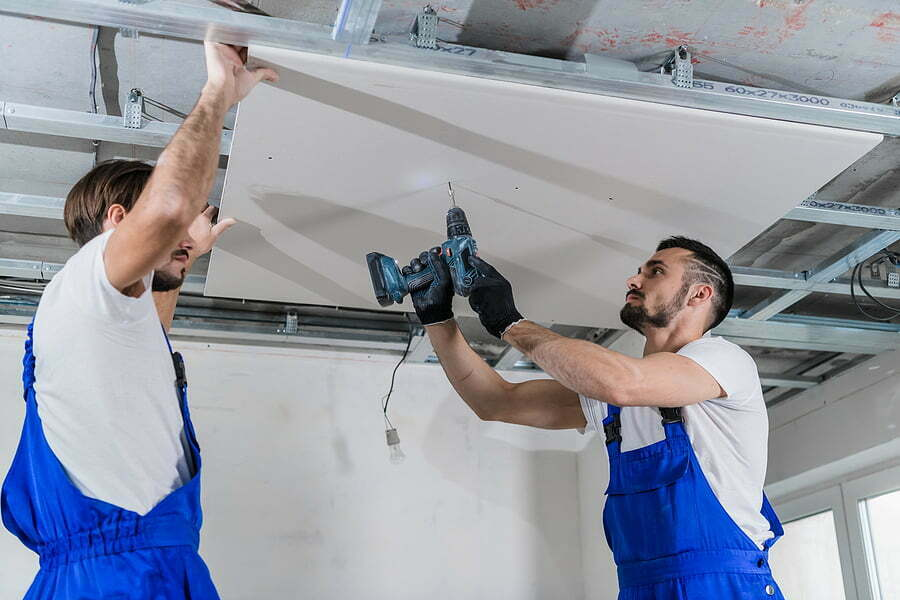 team of repairers are repairing the ceiling in an apartment