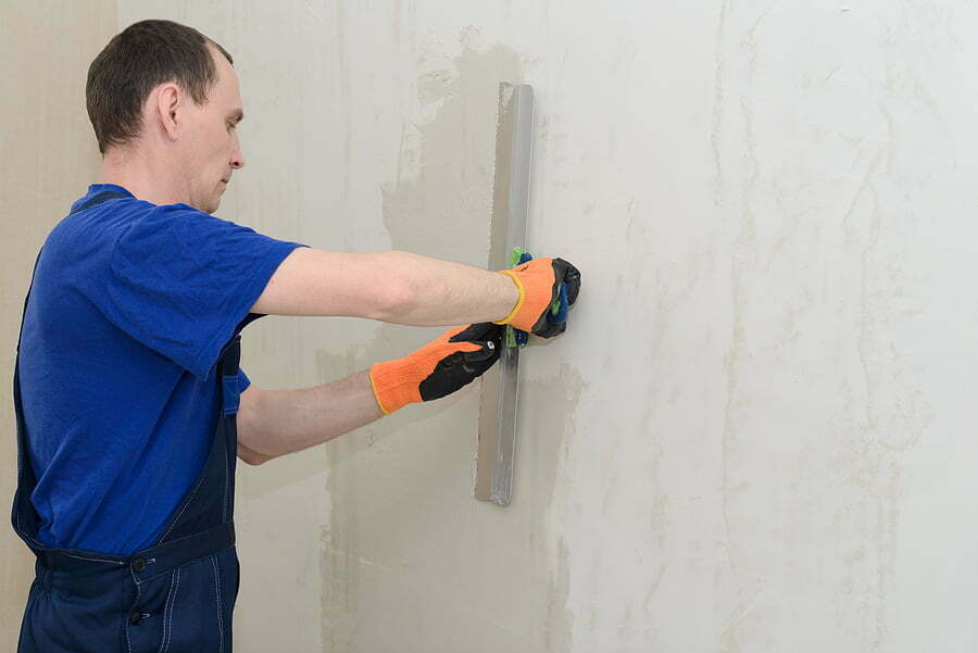 worker plastering a room wall with gypsum plaster