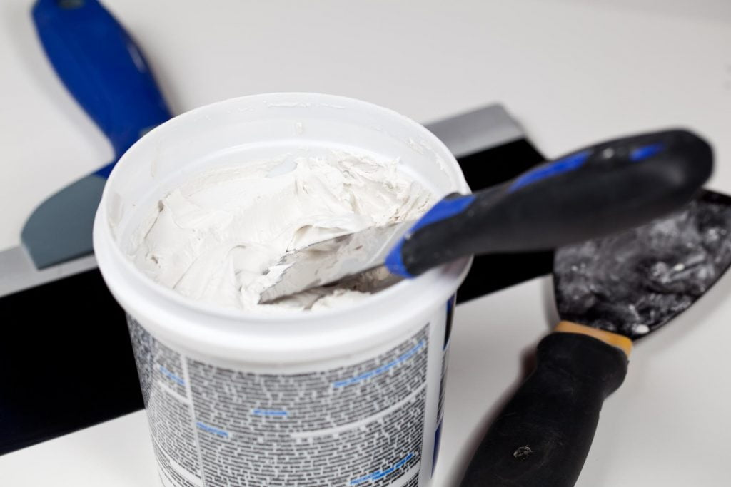 a can of putty and a spatula