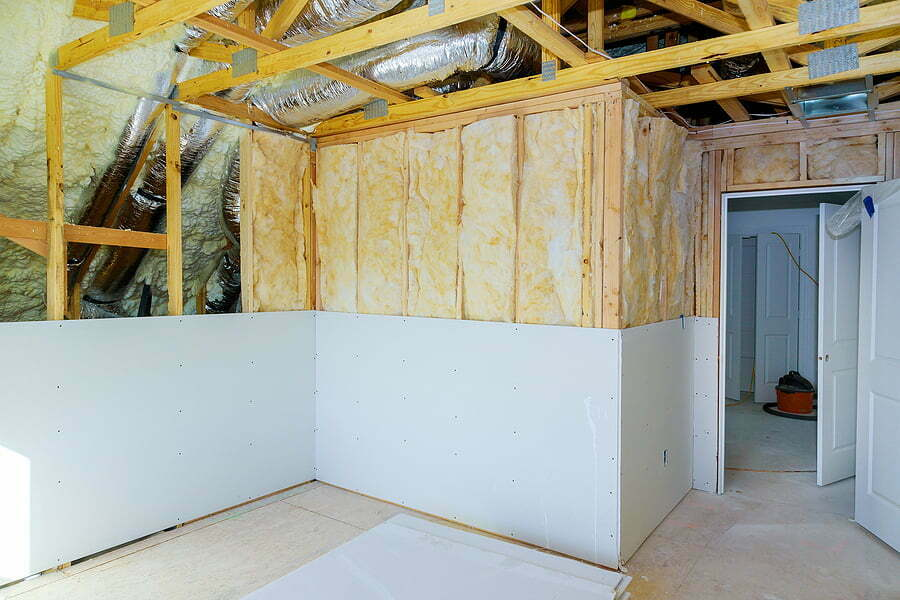 installing gypsum plasterboard sheet to wall for attic room construction at the attic polyurethane foam termal insulation