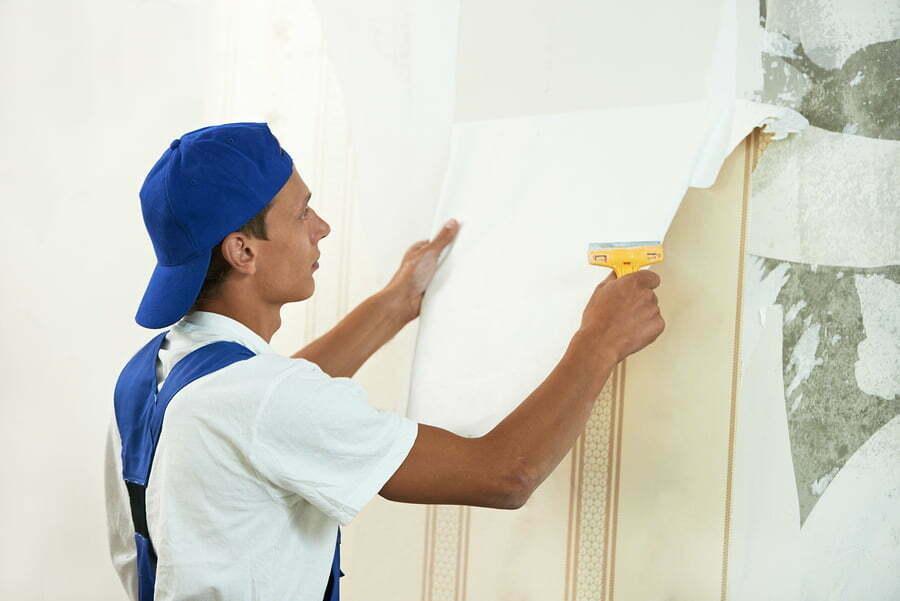 painter worker peeling off wallpaper during interior home repair renovation work